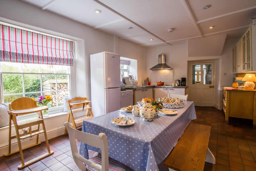 Kitchen laid out to be family friendly with high chairs and a large table to sit down and have meals with the family